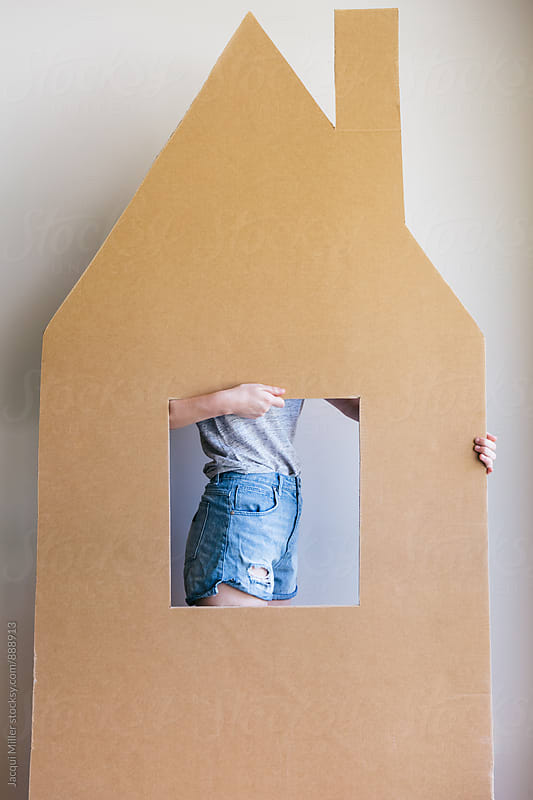 Unrecognisable female moving a large cardboard cut out of a house by Jacqui Miller for Stocksy United