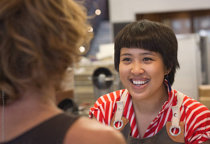 Employee Smiling at Customer by VISUALSPECTRUM for Stocksy United