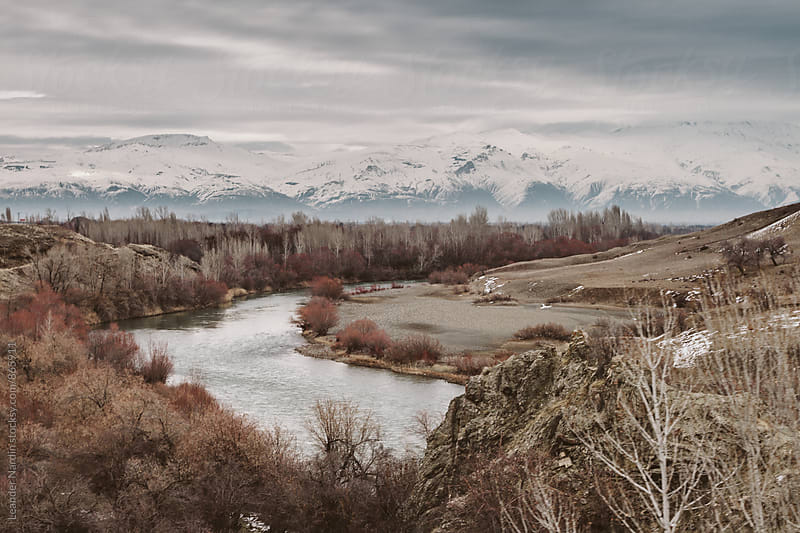 river flowing through snowcovered mountain landscape surrounded by colorful forest by Leander Nardin for Stocksy United