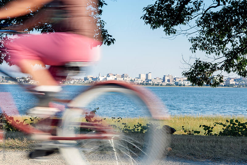 Woman on a pink bicycle rides past by Cara Dolan for Stocksy United