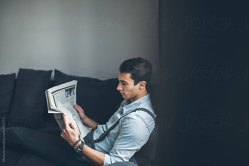 Young Man Reading Newspaper at Home by Mosuno for Stocksy United