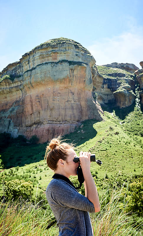 Young woman viewing a mountainous landscape through binoculars by Jacques van Zyl for Stocksy United