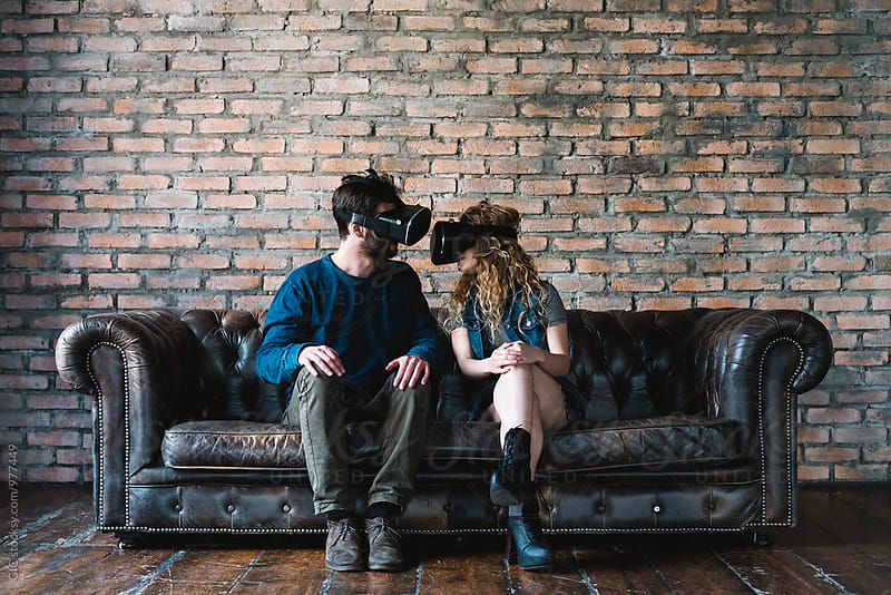 Couple at home using VR Reality viewer by Simone Becchetti for Stocksy United