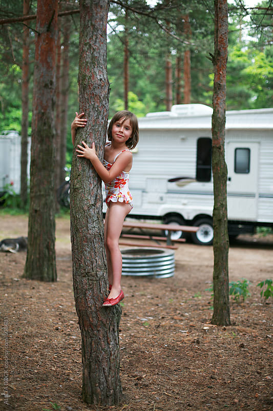 Funny Cute Girl Trying To Climb A Tree In A Bathing Suit and Fancy Shoes by ALICIA BOCK for Stocksy United