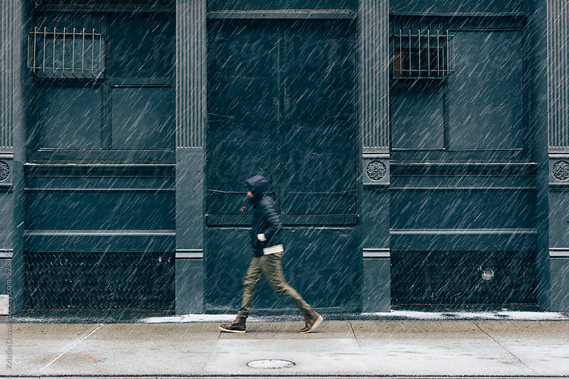 Man walking through snowstorm. Soho. New York City. by Kristin Duvall for Stocksy United