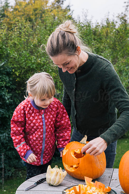 Mother and daugther carve pumpkins for Halloween by Lior + Lone for Stocksy United