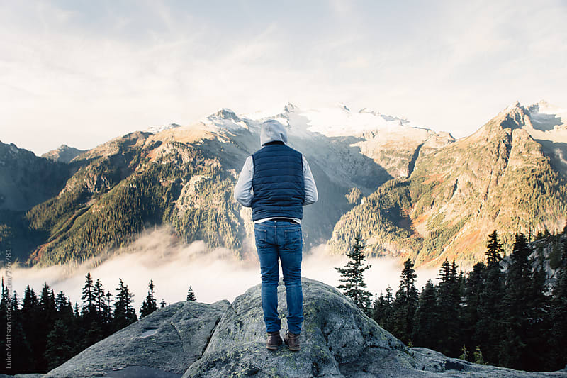 Young Man In Blue Jeans And Hoodie Standing On Top Of Ledge Looking At Mountains by Luke Mattson for Stocksy United
