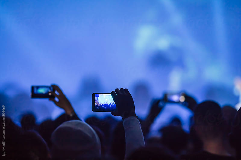 audience with mobile phones,performance,blue by Igor Madjinca for Stocksy United
