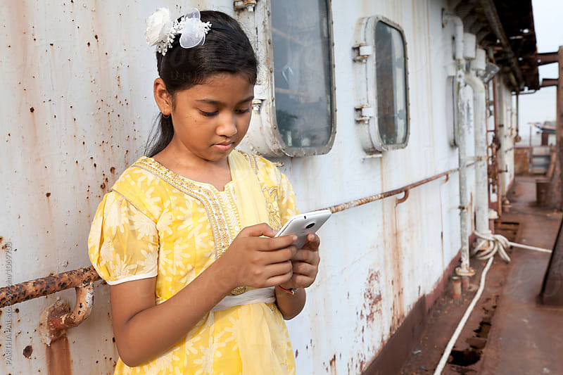 Teenage girl using smart phone by PARTHA PAL for Stocksy United