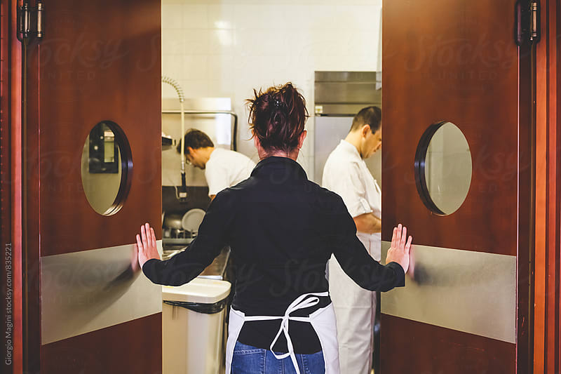 Waitress Opening the Doors of the Kitchen in a Restaurant by Giorgio Magini for Stocksy United