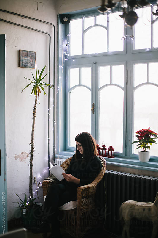 Woman reading a book in her home  by Marija Mandic for Stocksy United