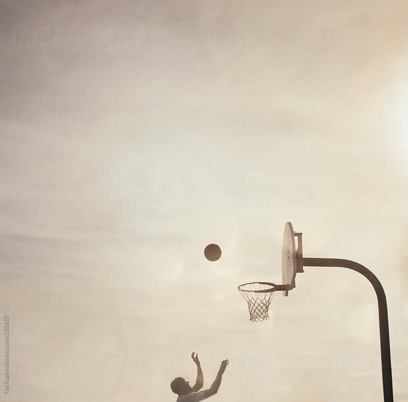 silhouette of man playing basketball by Tod Kapke for Stocksy United
