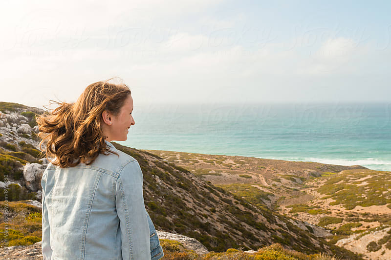 teen girl looking out to sea from a clifftop by Gillian Vann for Stocksy United