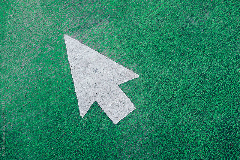 Arrow symbol on urban street and bike lane by Paul Edmondson for Stocksy United