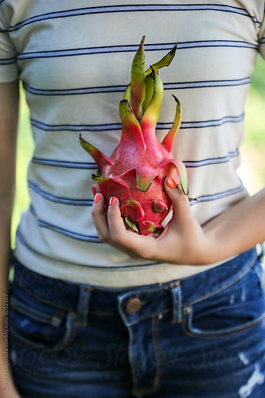 Teenage girl holding a pink dragon fruit by Carolyn Lagattuta for Stocksy United