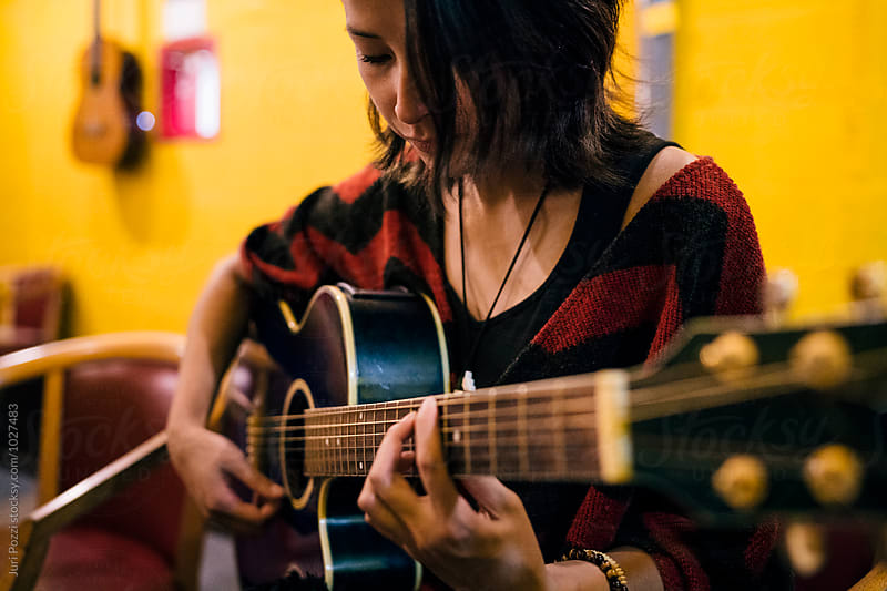 Asian woman playing the guitar by Juri Pozzi for Stocksy United