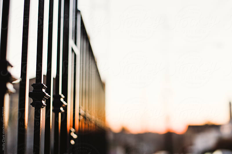 The reflection of a sunset on a city fence. by Holly Clark for Stocksy United