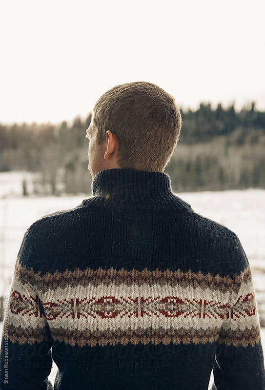 man in sweater looking at horizon by Shaun Robinson for Stocksy United