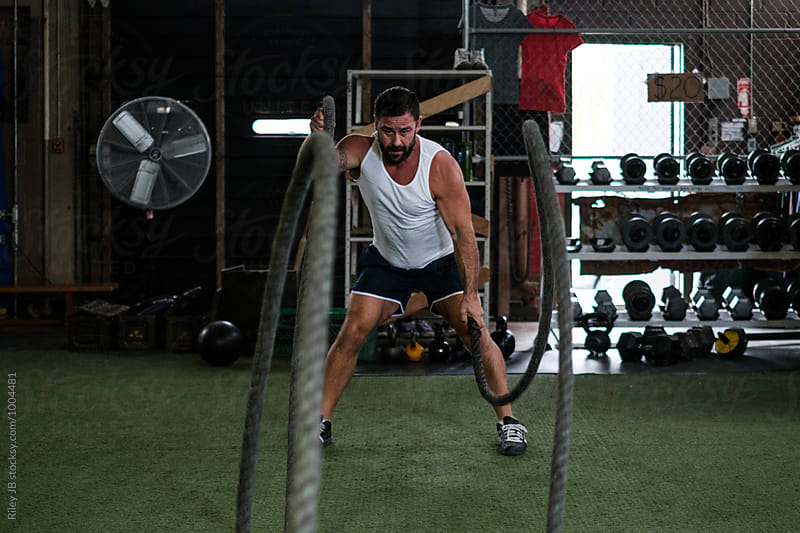 Muscular man works out with battling ropes by Riley J.B. for Stocksy United