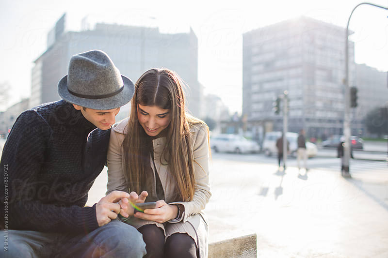 Affectionate couple using technology together outdoors by michela ravasio for Stocksy United