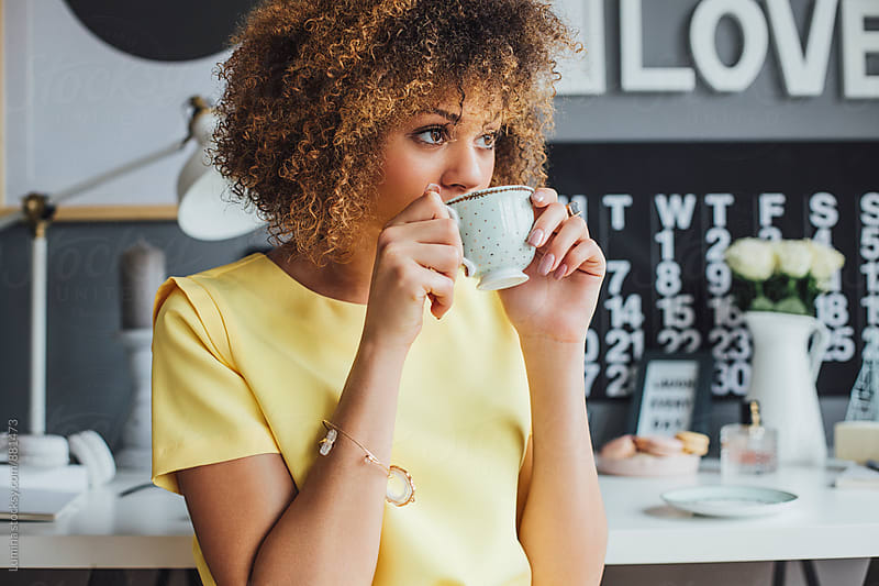 African Woman Drinking Coffee at Home by Lumina for Stocksy United