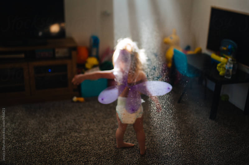 Toddler girl with butterfly wings playing in water droplets by Jessica Byrum for Stocksy United