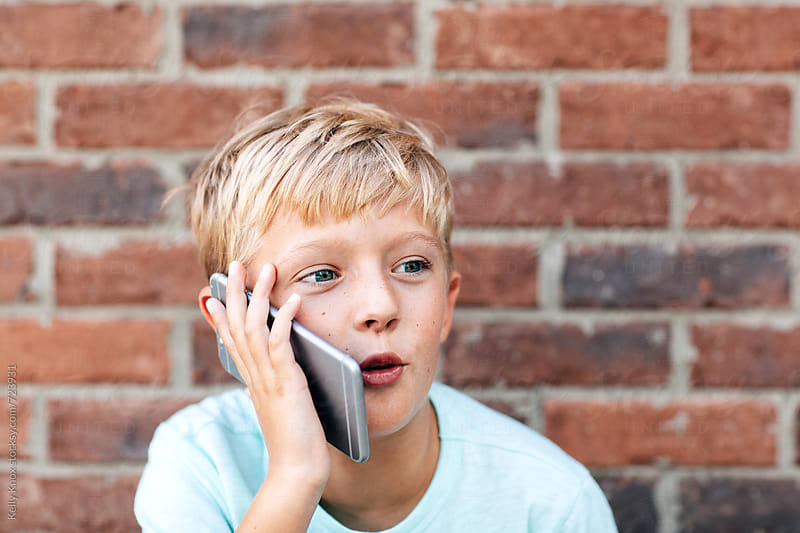 expressive boy talking on a phone by Kelly Knox for Stocksy United