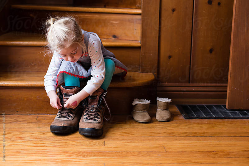 little girl tries on dad's shoes by Brian Powell for Stocksy United