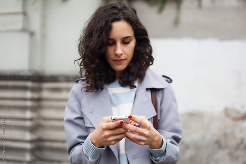 Stylish woman browsing on her mobile phone in the street  by Marija Mandic for Stocksy United