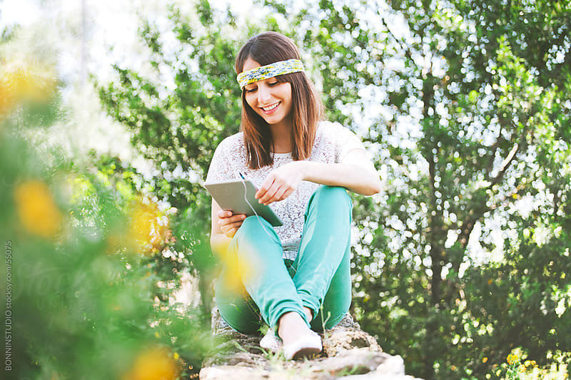 Young woman listening music and reading with digital tablet on a park. by BONNINSTUDIO for Stocksy United