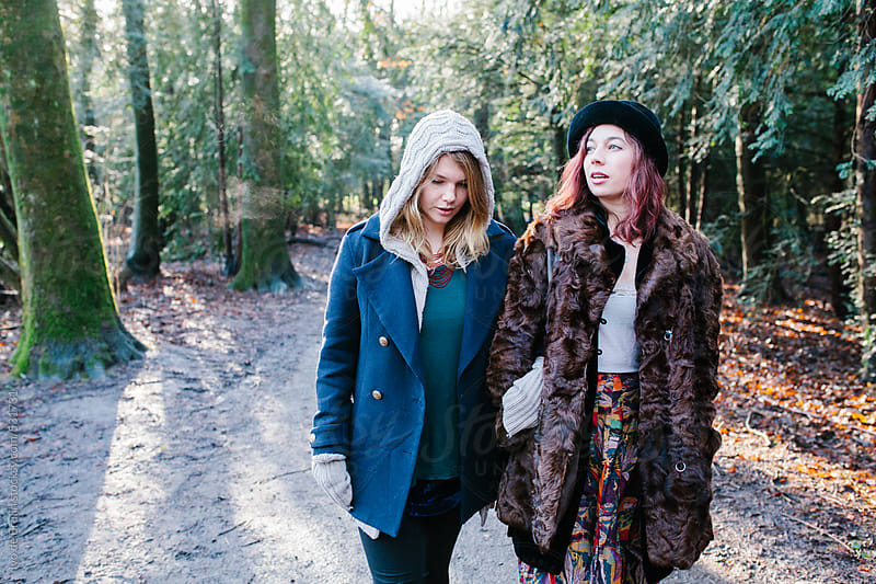Two young women and friends walking in the forest  by Ivo de Bruijn for Stocksy United