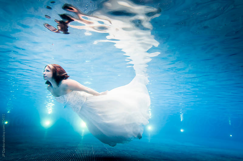 Trash the Dress Underwater Bride Swimming in Wedding Dress to Surface by JP Danko for Stocksy United