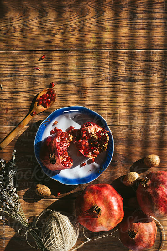 Pomegranate on a Wooden Table by Mosuno for Stocksy United