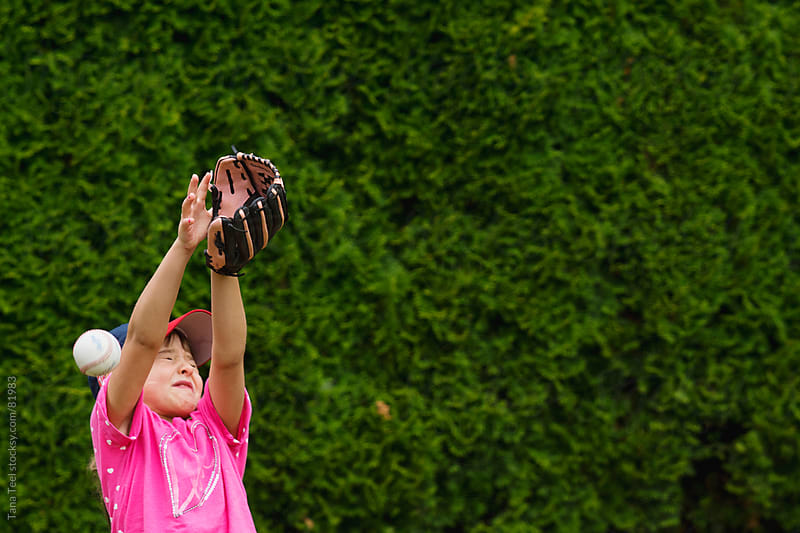 Young girl trying to catch a baseball by Tana Teel for Stocksy United
