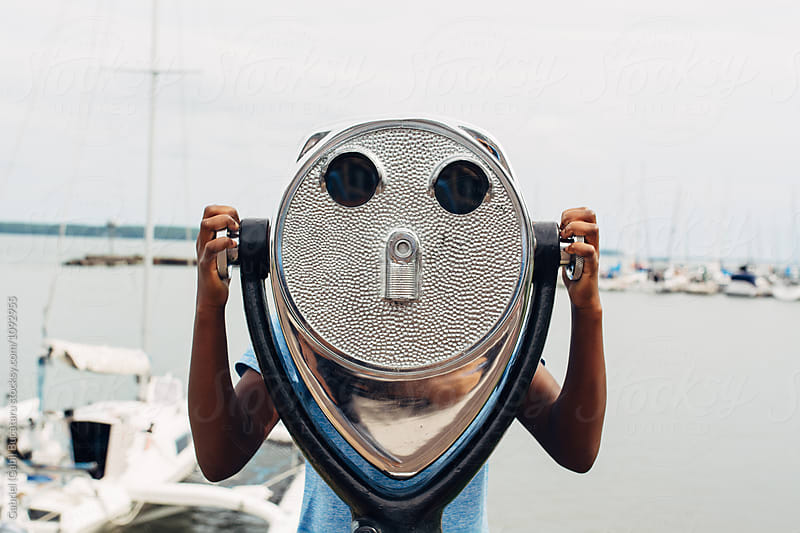 Black girl looking through binoculars by a bay by Gabriel (Gabi) Bucataru for Stocksy United