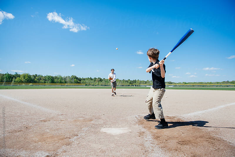 Boy prepares to swing bat as dad pitches baseball to him by Cara Dolan for Stocksy United