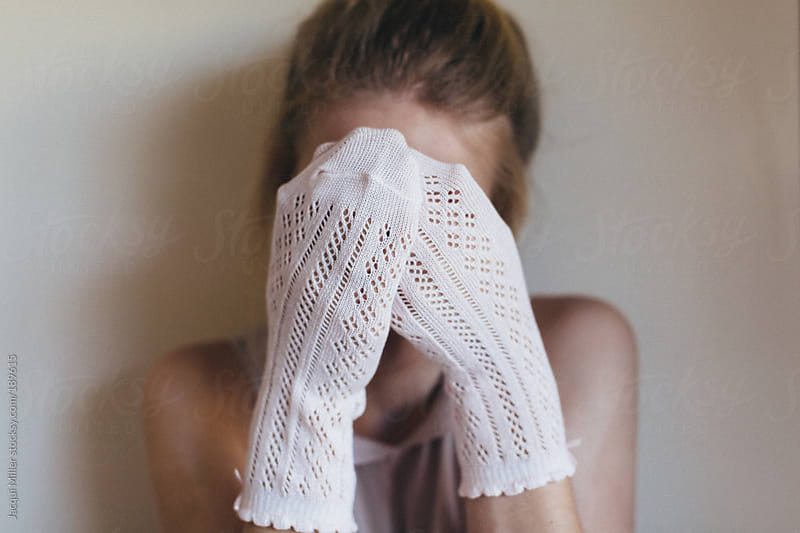 Playful girl hiding behind her hands by Jacqui Miller for Stocksy United