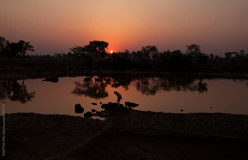 A girl bending fotrward in front of a waterbody and enjoying sunset by PARTHA PAL for Stocksy United