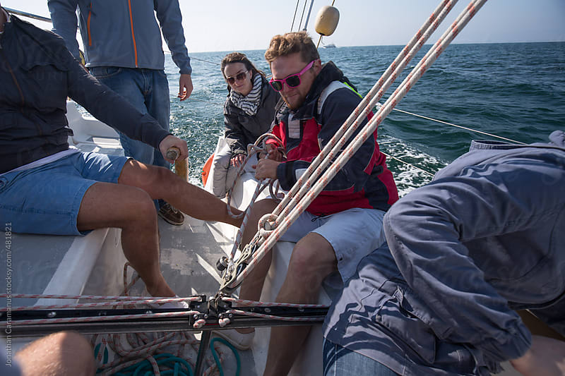 Crew on sail boat working together on rigging for ocean adventure by Jonathan Caramanus for Stocksy United