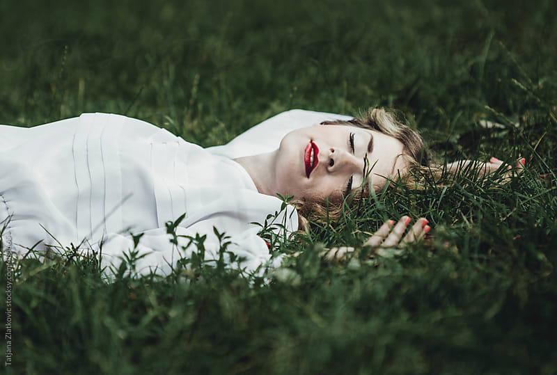 Beautiful girl laying down on grass by Tatjana Zlatkovic for Stocksy United