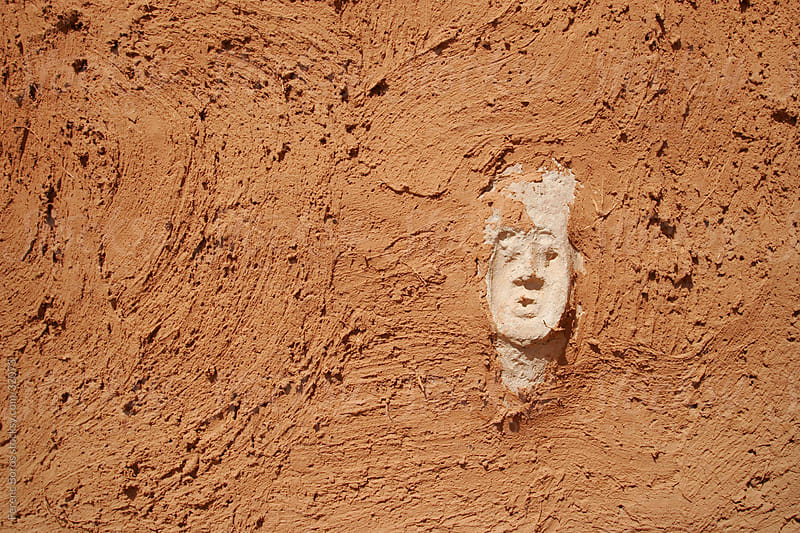 White face embedded in the red wall in a Dogon village, Africa by Ferenc Boros for Stocksy United