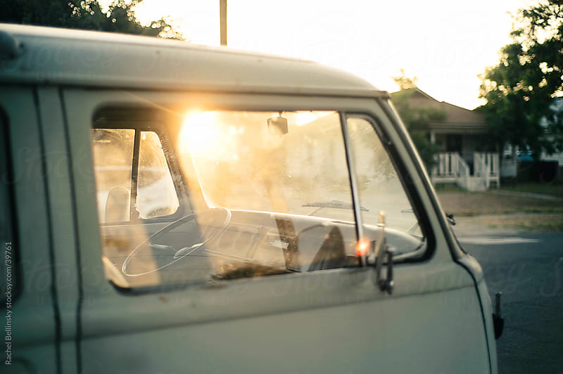 White vintage bus with sun flare in window by Rachel Bellinsky for Stocksy United