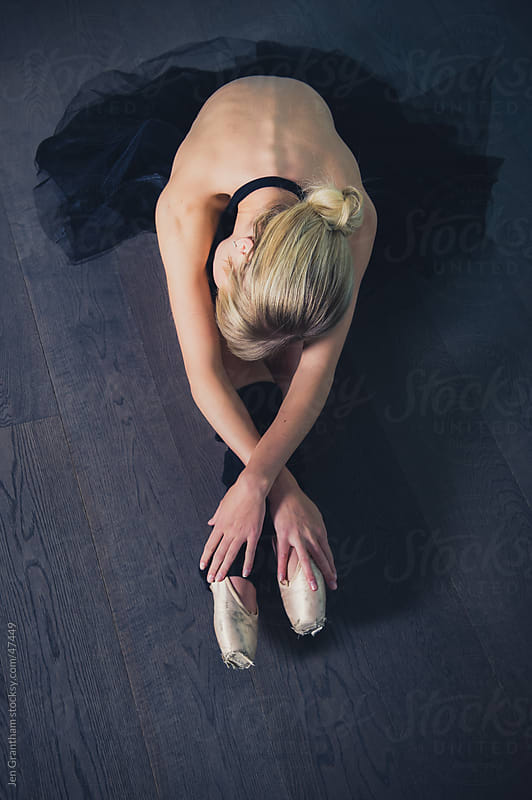 Ballerina stretching on the floor by Jen Grantham for Stocksy United