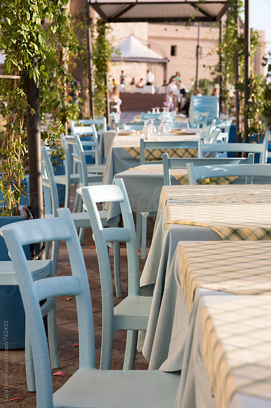 Tables and chairs outside in a patio by Luca Pierro for Stocksy United
