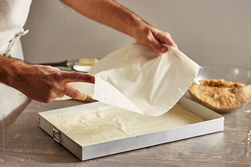 Man placing filo sheets into baking pan by Martí Sans for Stocksy United