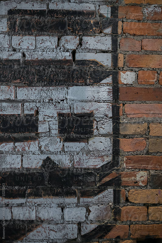 Old advertisment paint on brick wall by Rowena Naylor for Stocksy United