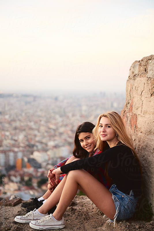 Two lovely young women sitting against of cityscape by Guille Faingold for Stocksy United