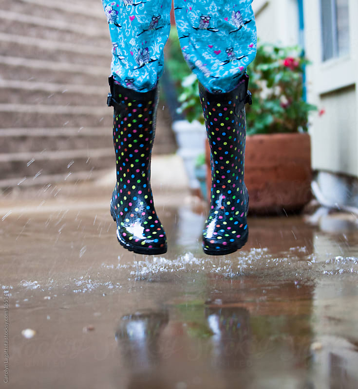 Little girl outside jumping in rain puddles and pajamas by Carolyn Lagattuta for Stocksy United
