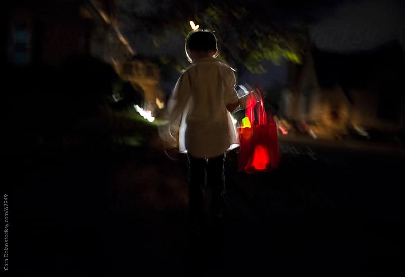 Boy with candy bag walks through a dark neighborhood on Halloween night by Cara Dolan for Stocksy United