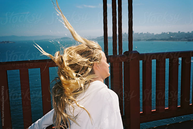 blonde girl teenager getting hair whipped by wind on golden gate bridge by wendy laurel for Stocksy United